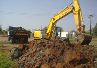 Excavator loading spoil material on a tipper truck in Block F, Soshanguve